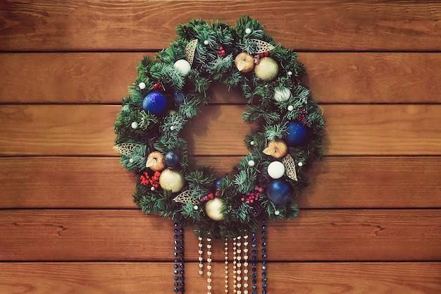 나무 배경에 손수 만든 크리스마스 화환입니다. 화환의 축제 조명입니다. 새해 인테리어 장식.