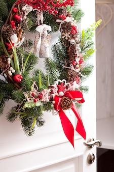 クリスマスリースは白いドアに掛かっています。赤と白の要素、休日の家を飾るための弓