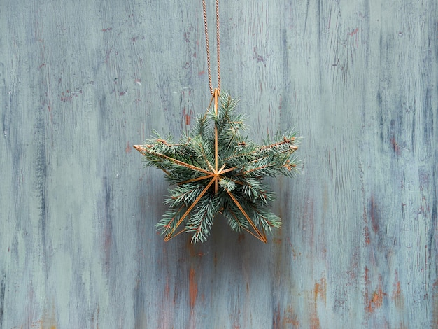 Рождественский венок в форме золотой геометрической звезды с еловыми ветками висят на деревенской деревянной двери, традиционный рождественский орнамент.