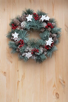 Christmas wreath on light wooden background. christmas pattern. copy space. vertical frame.