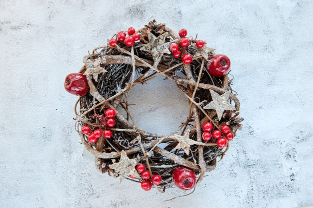 Christmas wreath made of branches decorated with gold wooden stars and red berry bubbles on cement background