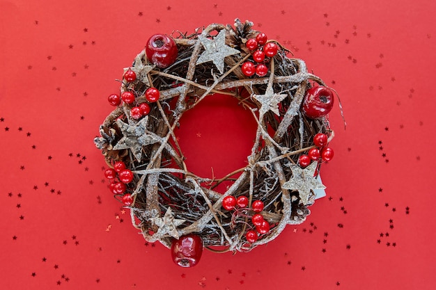 Christmas wreath made of branches decorated with gold wooden stars and red berry bubbles isolated on red background.