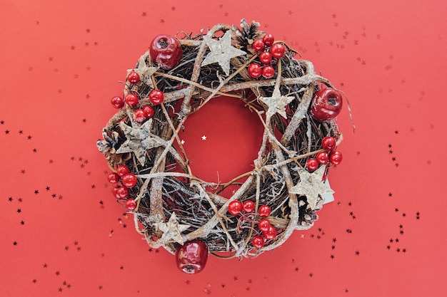 Christmas wreath made of branches decorated with gold wooden stars and red berry bubbles isolated on red background