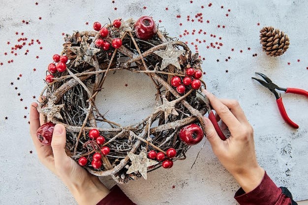 Christmas wreath made of branches decorated with gold wooden stars and red berry bubbles.