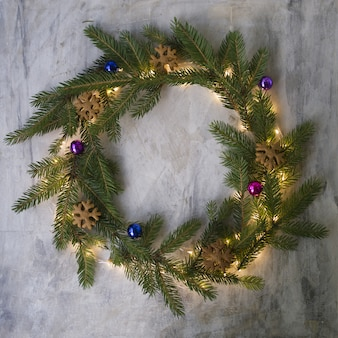 Christmas wreath made of fir branches, cookies, colored balls and glowing lights.