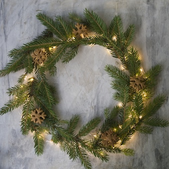 Christmas wreath made of fir branches, cookies and glowing lights on gray background.