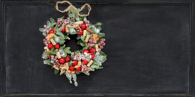 Christmas wreath made of fir branches, dried apples, cinnamon, red berries, bottle caps, red balls hanging on a black chalk board.
