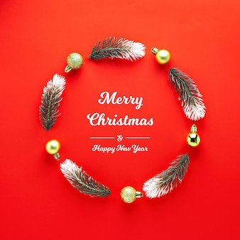 Christmas wreath made of fir branches new year tree balls on red background