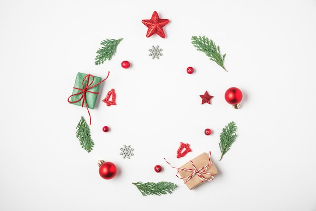 Christmas wreath made of fir tree branches, red decorations, gift boxes, pine cones on white background