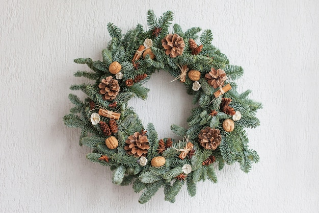 Christmas wreath made of natural fir branches  hanging on a white wall.