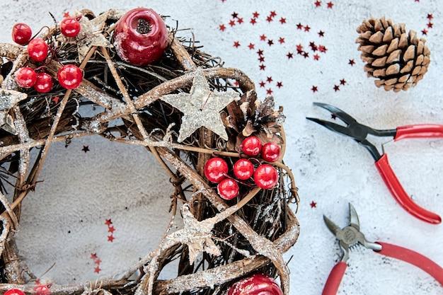 クリスマスリース金の木製の星と赤いベリーの泡で飾られた枝でできています。クリエイティブなdiyクラフトの趣味。手作りのクリスマスデコレーションを作ります。金属ペンチ、ニッパーを備えたトップビュークラス