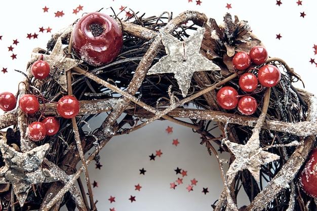 クリスマスリース白い背景に金の木製の星と赤いベリーの泡で飾られた枝で作られました。クリエイティブなdiyクラフトの趣味。コピースペースのある上面図