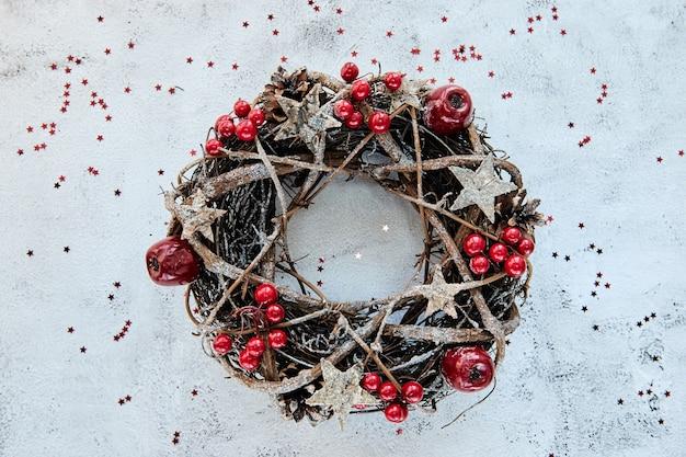 金の木製の星で飾られた枝で作られたクリスマスリース