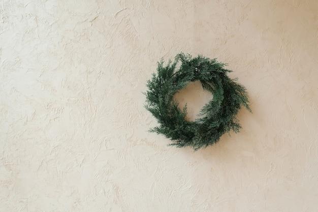 コピースペースとベージュの背景に針葉樹で作られたクリスマスリース