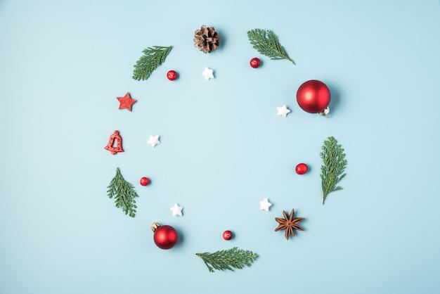 モミの木の枝、赤い装飾、冬の果実、青の背景に松ぼっくりのクリスマスリース