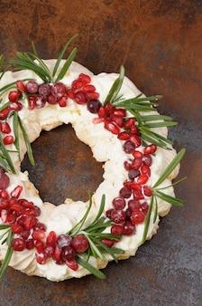 クリーム、ザクロ、クランベリー、ローズマリーのクローズアップとメレンゲで作られたクリスマスリース