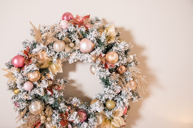 베이지 색 벽에 걸려 자연 전나무 가지로 만든 크리스마스 화 환.
