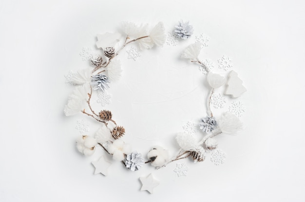 Christmas wreath made of wooden snowflakes, cotton flowers, pine cones and white flower pompons.