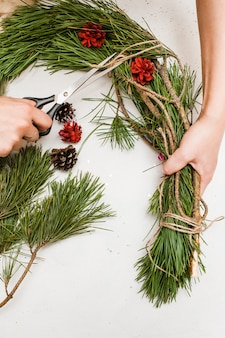 Рождественский венок делает женщина