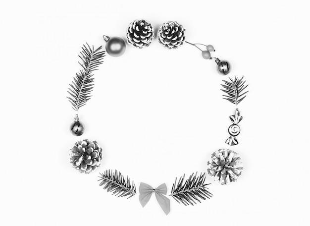 クリスマスのおもちゃ、コーン、モミの枝が白い背景で隔離のクリスマスリース。