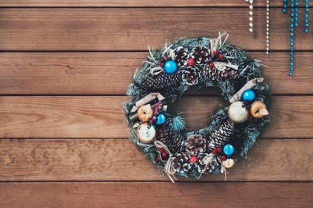 コーン、トウヒの枝とベリーのクリスマスリース、新年の装飾。コーン、ボール、フルーツの美しいトウヒの花輪。