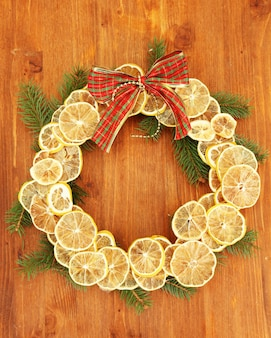木製のテーブルの上に、モミの木と弓と乾燥レモンのクリスマスリース