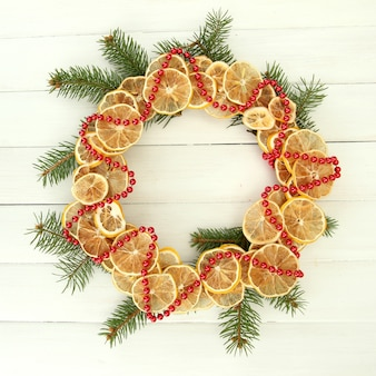 白い木製の背景に、モミの木と乾燥レモンのクリスマスリース