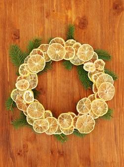Рождественский венок из сушеных лимонов с елкой, на деревянных фоне