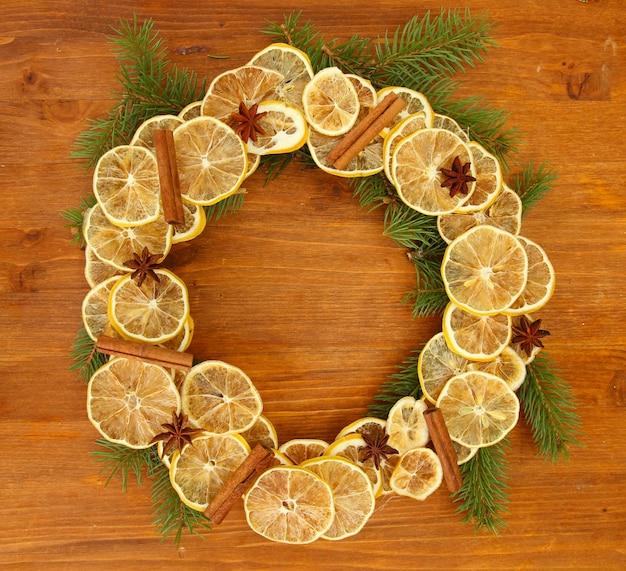 木製の表面にモミの木と乾燥レモンのクリスマスリース