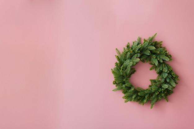 コピースペースと明るいピンクの背景にモミの枝のクリスマスリース