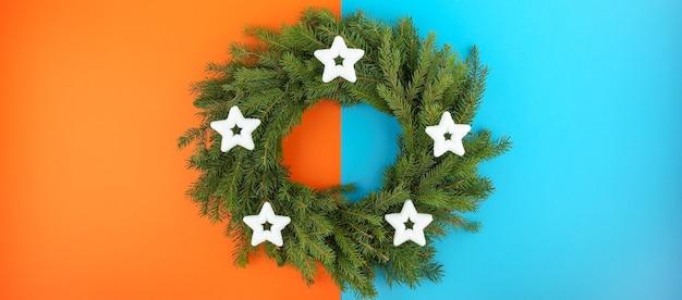 両側にコピースペースがある二重オレンジブルーの背景にモミの枝のクリスマスリース