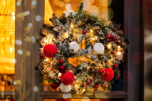 Рождественский венок из еловых веток с круглыми шарами красно-белого и золотого цветов
