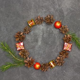 モミの実、枝、赤いおもちゃのクリスマスリース。黒の背景。コピースペース。フラットレイ