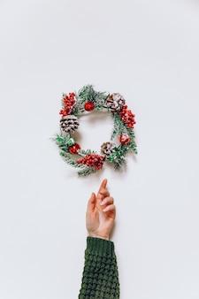 가문비 나무의 크리스마스 화환과 미니멀 한 스타일의 여성 손.