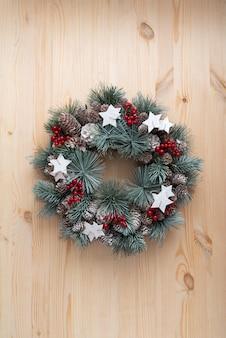 明るい木製の背景にクリスマスリース。クリスマスのパターン。垂直フレーム。