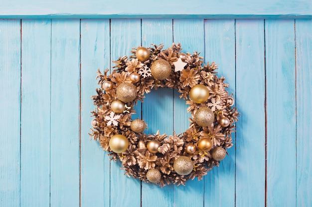 Рождественский венок на старой синей деревянной стене