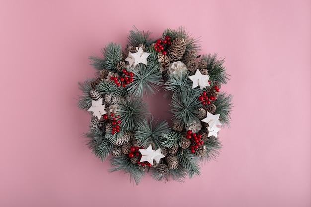 ピンクの背景にクリスマスリース。新年の飾り。クリスマスの飾り。