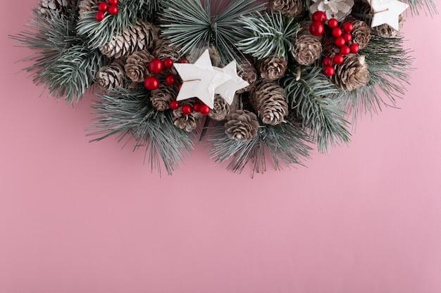 Рождественский венок на розовом фоне. новогодний образец. скопируйте пространство.