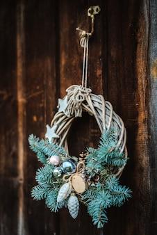 푸른 나무의 소박한 나무로되는 문 배경에 크리스마스 화 환.