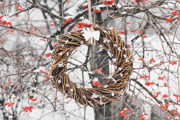 木の上のクリスマスリース。冬のベリーを背景にしたドアの手作りの花輪。冬の装飾。冬のガマズミ属の木