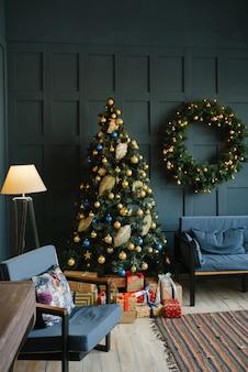 파란 벽과 거실에서 벽, 가문비 나무와 소파에 크리스마스 화환