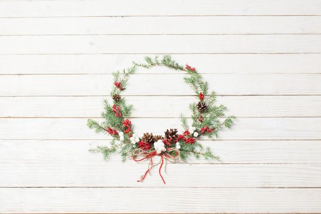 Рождественский венок на белой деревянной поверхности