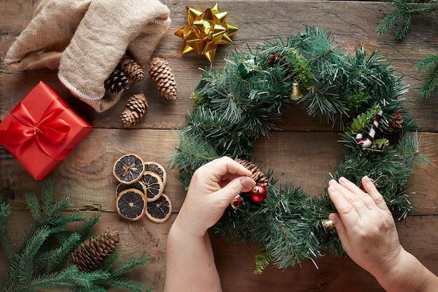 Рождественский венок на деревянных фоне. бабушкины руки.