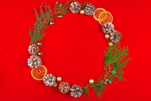 빨간색 배경에 콘과 소나무에서 크리스마스 화 환