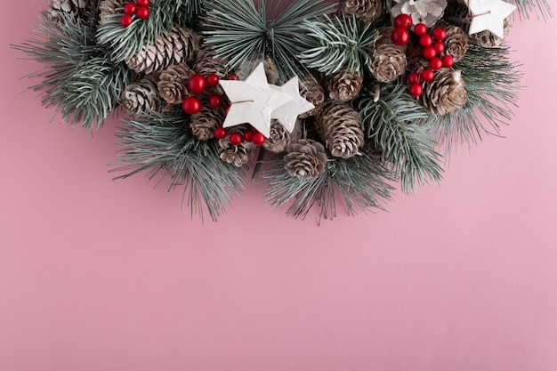 Christmas wreath on pink background. new year pattern. copy space.