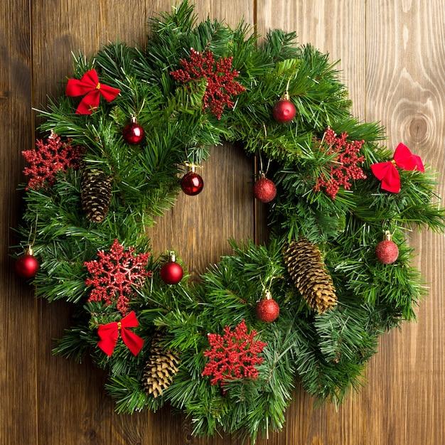 Christmas wreath on a rustic wooden front door - image