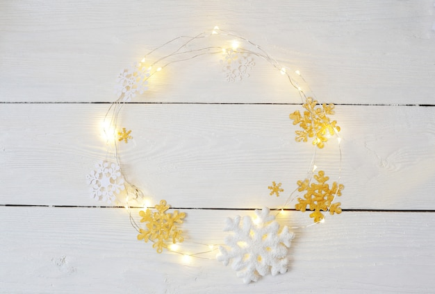 Christmas wreath of snowflakes and garlands on a white wood