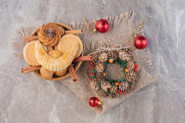 Рождественский венок, елочные украшения и кондитерская корзина на мраморе.