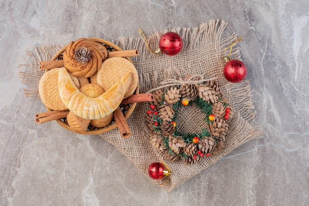 Christmas wreath, tree decorations and a pastry basket on marble.