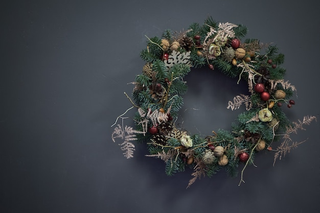 Christmas wreath of vines decorated with fir branches, christmas balls and natural materials,